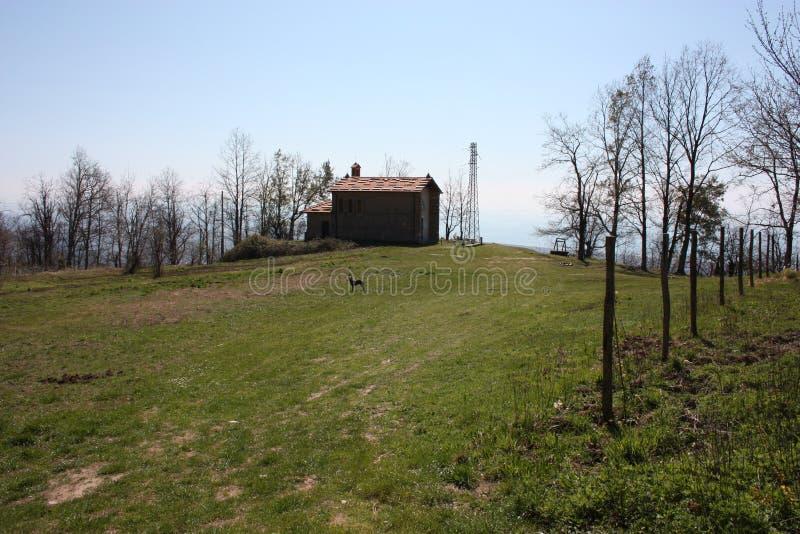 Liten kyrka som överges, i obruklighet, på de Apuan fjällängarna av den Tuscan Apenninesen i en röjning på en solig vårdag arkivfoto