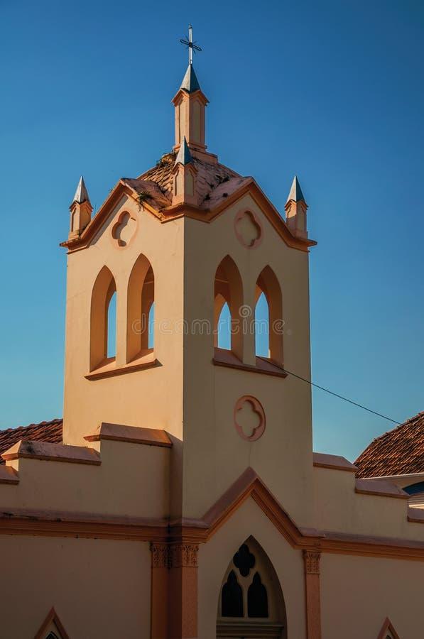 Liten kyrklig fasad och klockstapel med solljus på en sida och skugga på annan, på solnedgången i São Manuel fotografering för bildbyråer