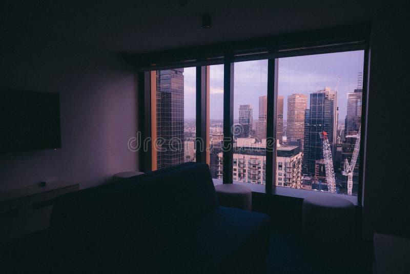 Liten lägenhet med ett stort fönster med en sikt av en stads- stadsarkitektur arkivfoton