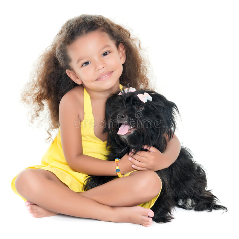 Liten latinamerikansk flicka som kramar hennes älsklings- hund royaltyfri fotografi