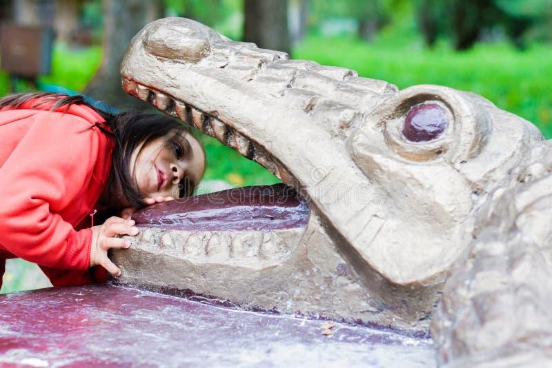 Liten latinsk flicka som loling in i munnen av monumentet av en krokodil royaltyfria foton