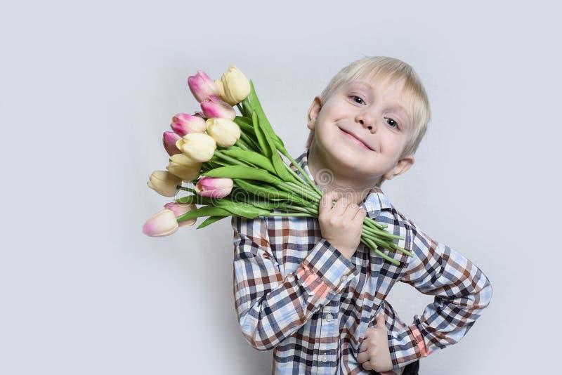 Liten le blond pojke som rymmer en bukett av tulpan ljus stående för bakgrund fotografering för bildbyråer