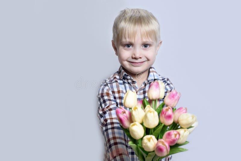 Liten le blond pojke som rymmer en bukett av tulpan ljus stående för bakgrund royaltyfri fotografi