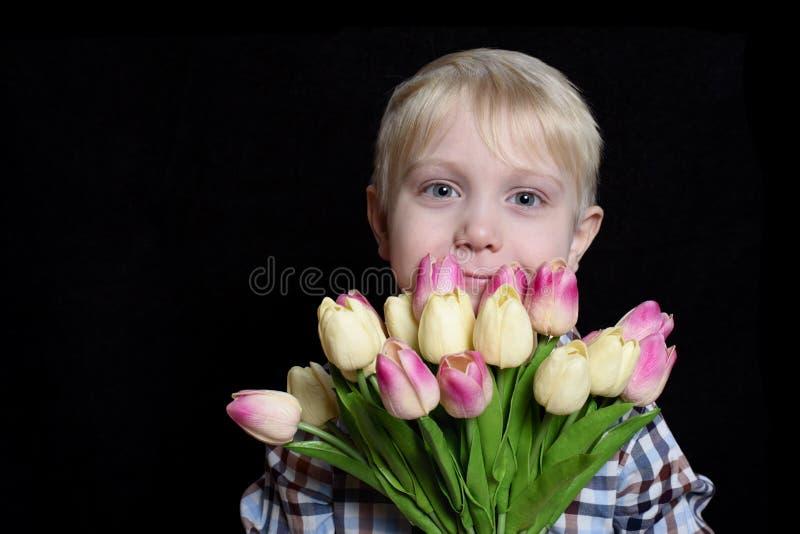 Liten le blond pojke som rymmer en bukett av tulpan Stående Isolat på svart bakgrund arkivfoto