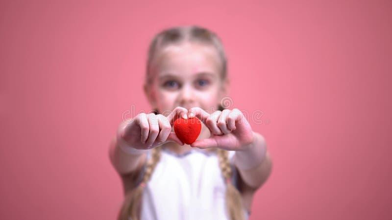 Liten le flicka med flätade trådar som visar leksakhjärta på kameracloseupen, välgörenhet arkivfoton