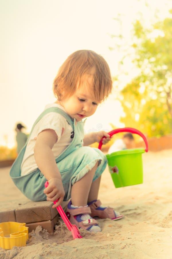 Liten le flicka som spelar med sand i sandlåda i sommar arkivbild