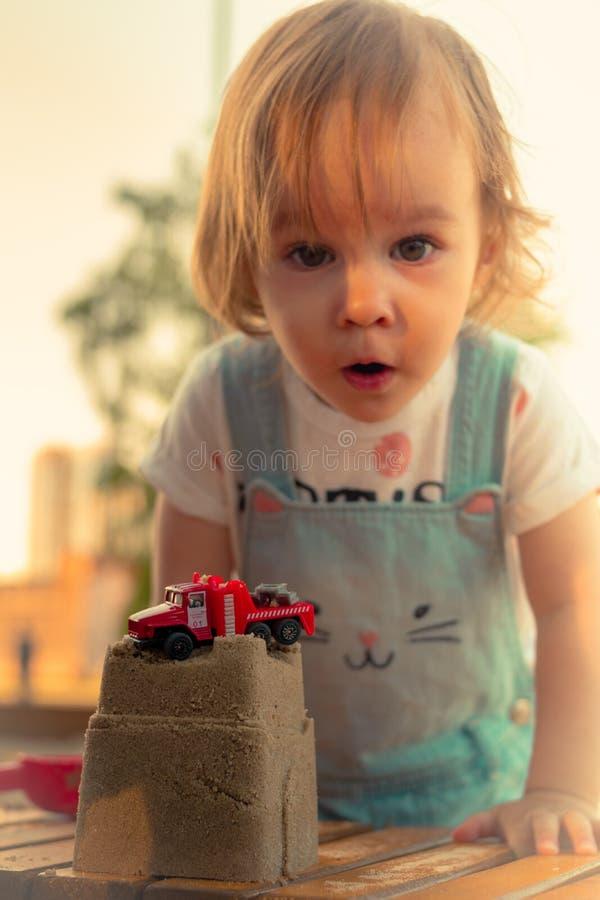 Liten le flicka som spelar med sandslotten och den röda billeksaken i sandlåda arkivbilder