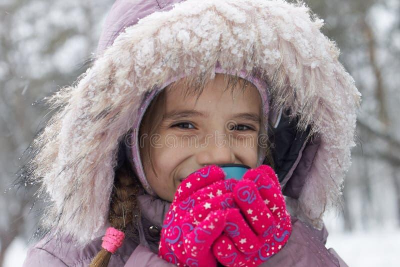 Liten le hoad tea för flickan drinken i vinter parkerar royaltyfri fotografi