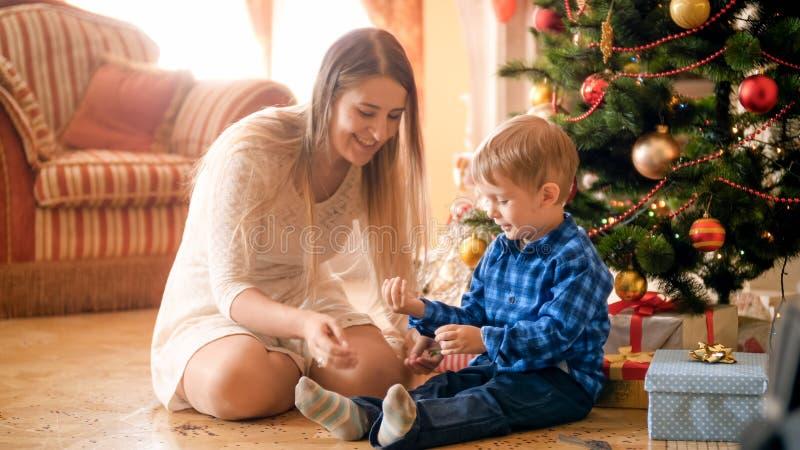 Liten le pojke med barnmodern i vardagsrum på julmorgonen arkivbild