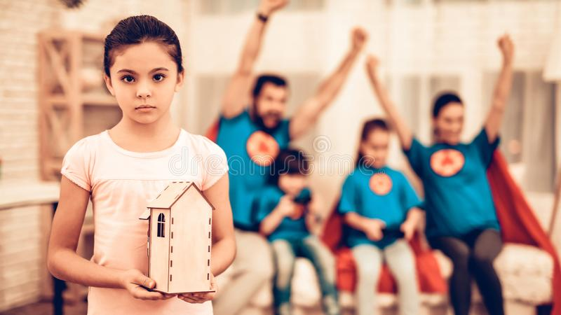 Liten ledsen flicka som visar Toy House nära den gulliga familjen arkivbild