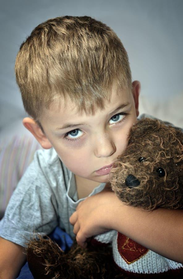 Liten ledsen pojke med ögonblåmärket och nallebjörn royaltyfria bilder