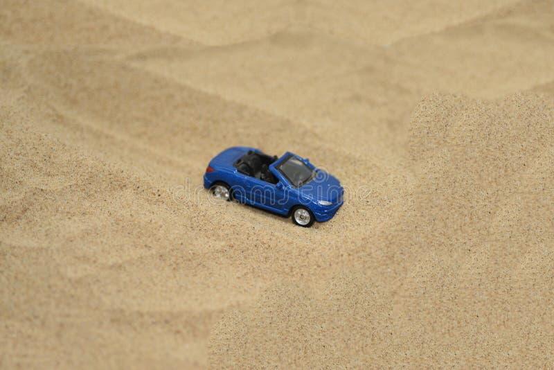 Liten leksakbil i gul sand arkivbild