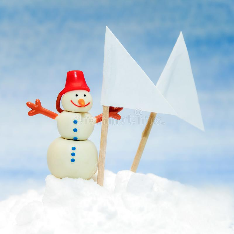 Liten leksaksnögubbe med två vita flaggor med stället för text royaltyfri foto