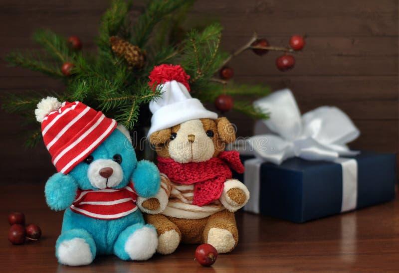 Liten leksakvovvar och nallebjörn, gåvaaskar, muttrar och julgranfilialer på en gammal träbakgrund royaltyfria foton