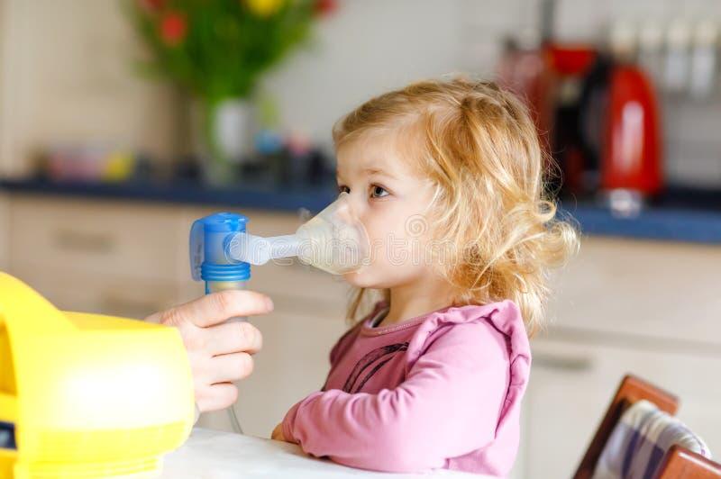 Liten litet barnflicka som hemma gör inandning med nebulizeren Fader eller moder som hjälper och rymmer apparaten barn royaltyfria foton