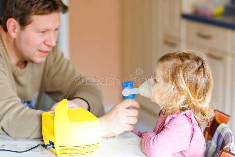 Liten litet barnflicka som hemma g?r inandning med nebulizeren Fader som hj?lper och rymmer apparaten Barn som har influensa arkivbilder
