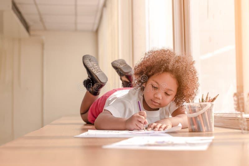 Liten litet barnflicka som l?gger ner koncentrat p? teckning Afrikansk flicka f?r blandning att l?ra och spela i f?rtr?ningsgrupp royaltyfri foto