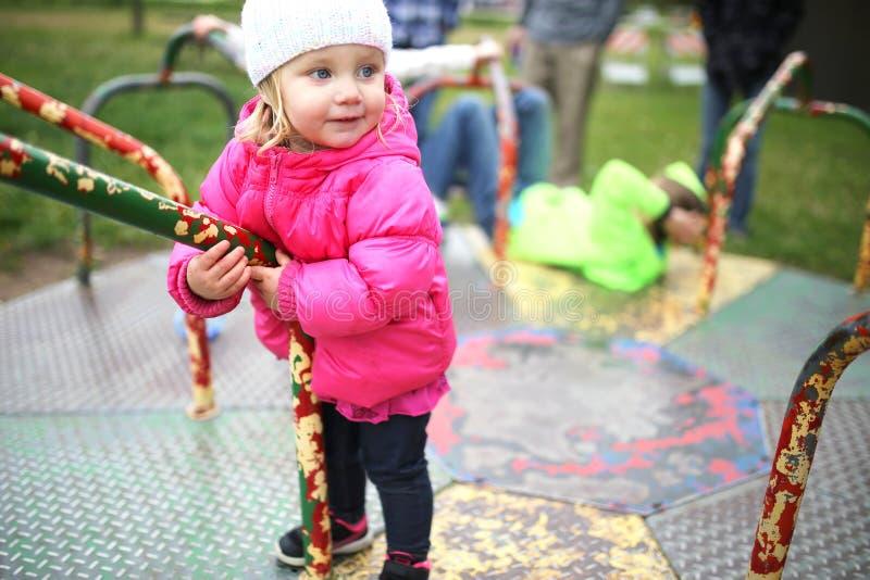 Liten litet barnflicka som spelar på karusell på lekplatsen fotografering för bildbyråer