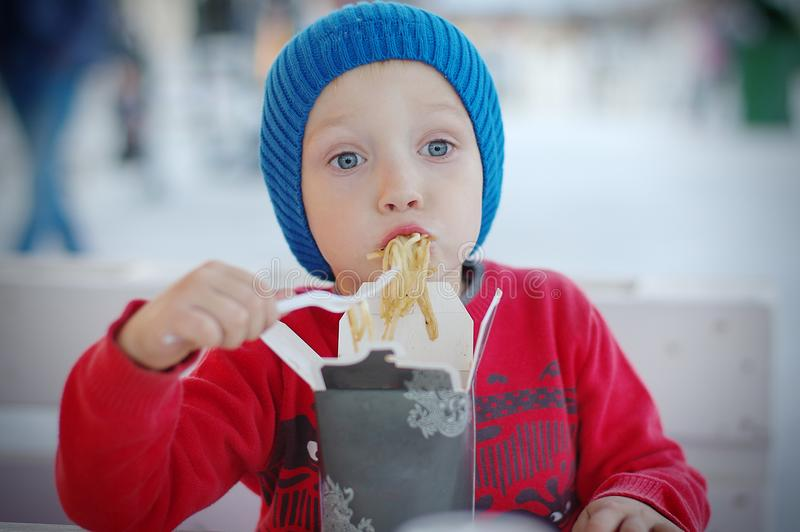 Liten litet barnpojke som äter asiatisk mat för lunch royaltyfri bild