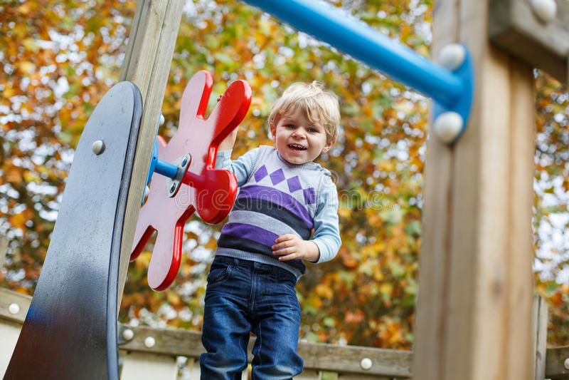 Liten litet barnpojke som har gyckel på lekplats i höst royaltyfri fotografi
