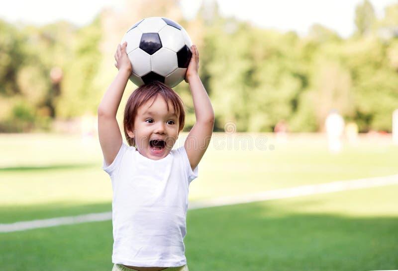 Liten litet barnpojke som spelar fotboll på fotbollfält utomhus: ungen rymmer bollen ovanför huvudet och att ropa som är klara at royaltyfri foto