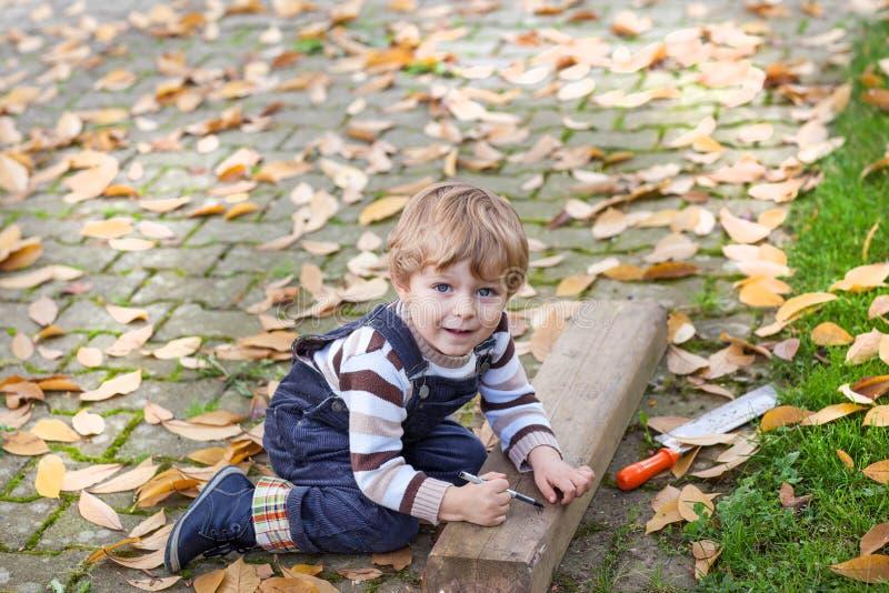 Liten litet barnpojke som spelar i höstträdgård royaltyfria bilder