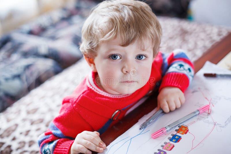 Liten litet barnpojketeckning med färgrika pennor arkivfoto