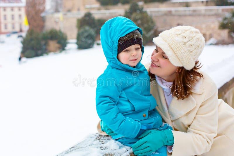 Liten litet barnungepojke och moder som har gyckel med snö på vinterdag royaltyfri foto
