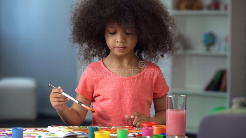 Liten lockig afrikansk flicka som målar en bild och ler, lycklig barndom royaltyfria foton