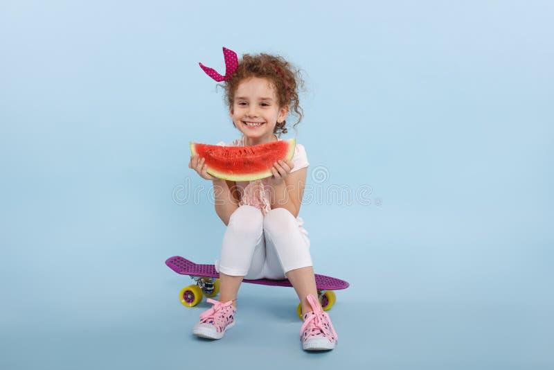 Liten lockig haired flicka för lycka med vattenmelon i händer som placeras på en skateboard som isoleras på en blå bakgrund royaltyfria foton