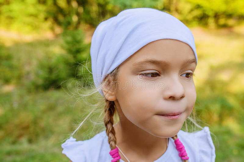 Liten lugna flicka i den vita halsduken i profil royaltyfri bild