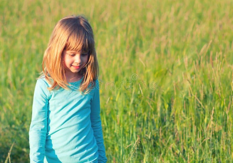 Liten lycklig blond flicka som går på ängen på den soliga våren royaltyfria foton