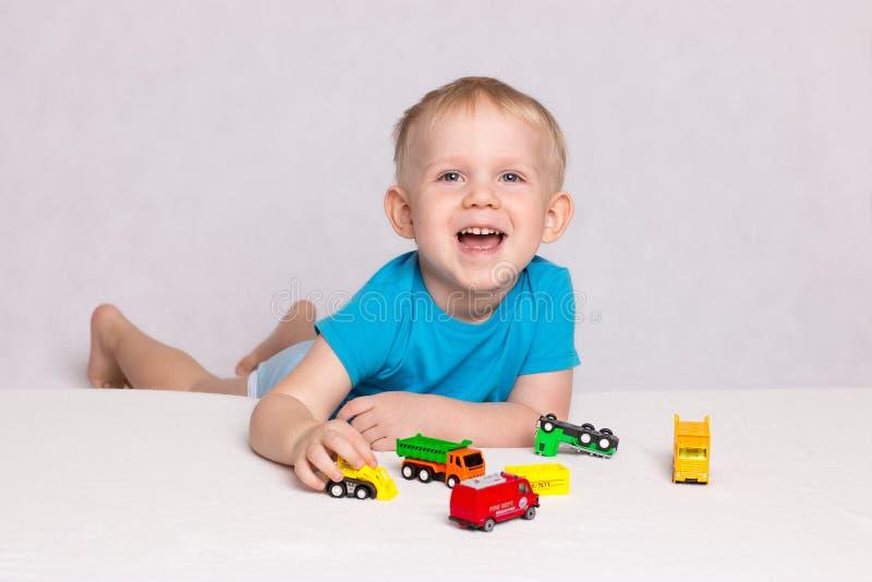 Liten lycklig blond pojke som spelar kulöra bilar på vit bakgrund royaltyfri bild