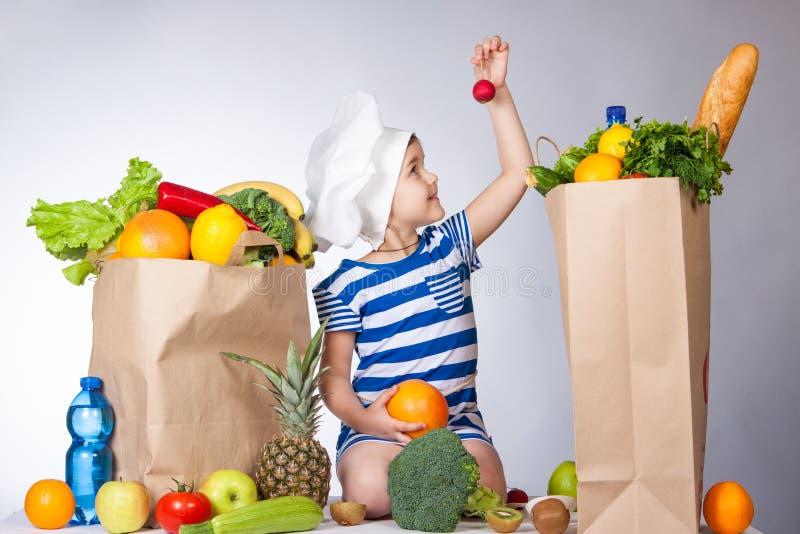 Liten lycklig flicka i hatten av kocken med stora påsar av mat En variation av nya frukter och grönsaker i påsar på tabellen Hea royaltyfria foton