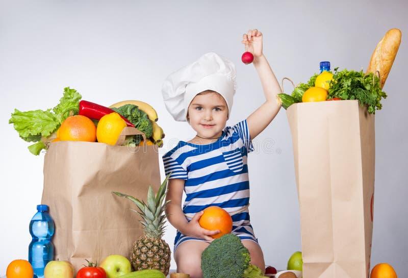 Liten lycklig flicka i hatten av kocken med stora påseprodukter som rymmer en rädisa En variation av nya frukter och grönsaker i  arkivbilder