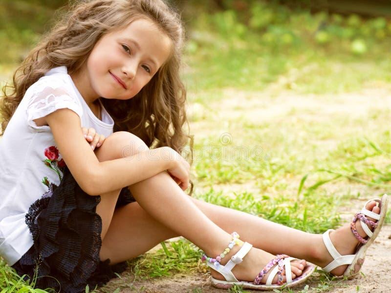 Liten lycklig flicka i trädgård fotografering för bildbyråer
