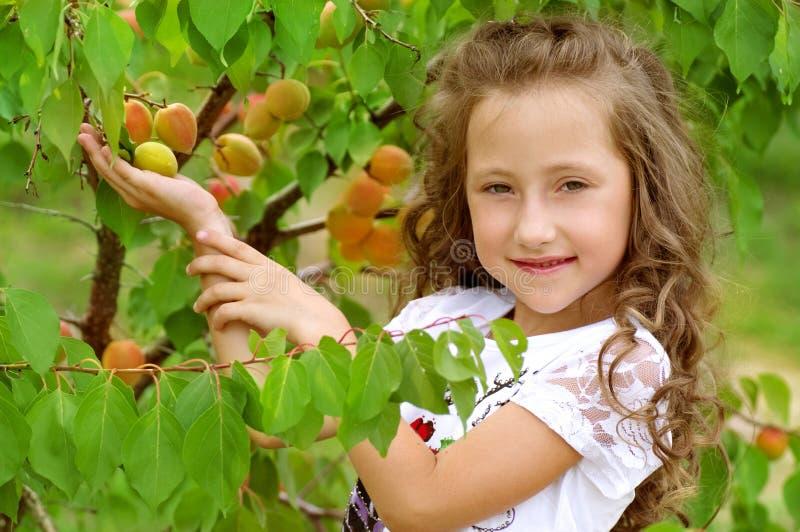 Liten lycklig flicka i trädgård arkivfoton