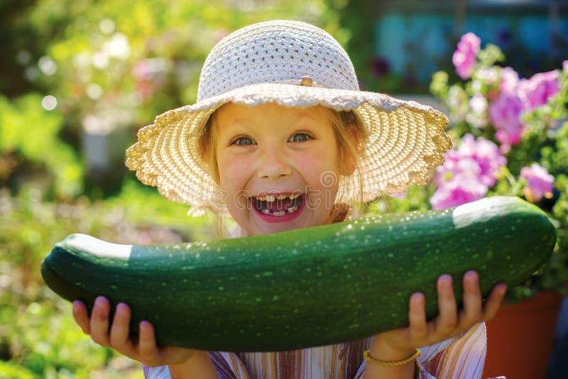 Liten lycklig flicka med zucchinin i händerna av royaltyfria foton