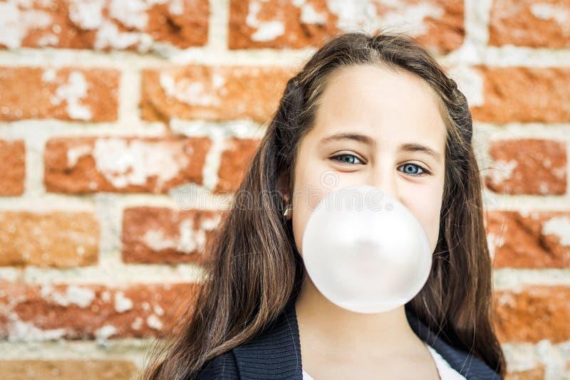 Liten lycklig flicka som blåser ett tuggummi arkivbild