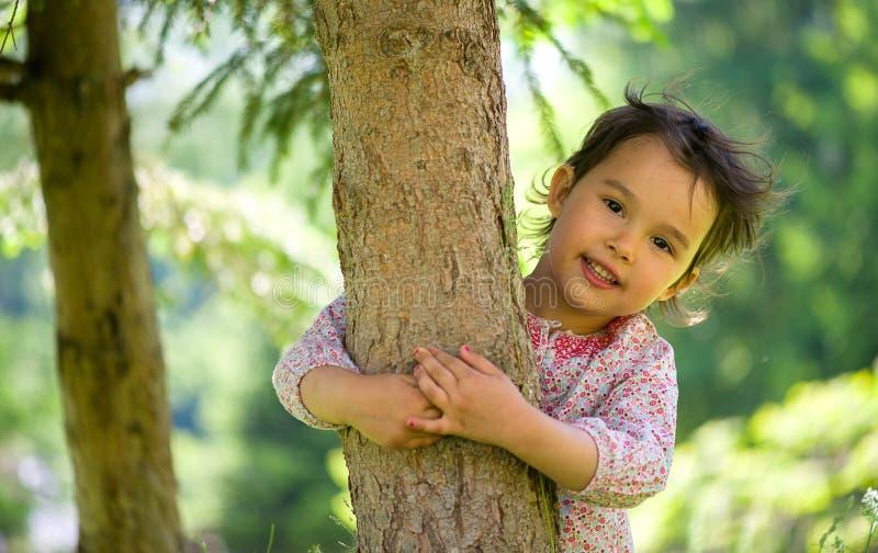 Liten lycklig flicka som kramar ett träd i sommartid royaltyfri bild