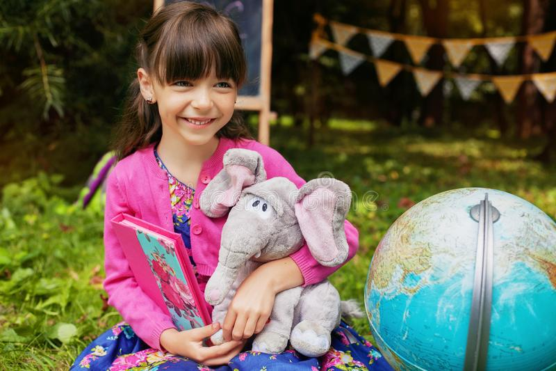 Liten lycklig flicka som spelar och lär tillbaka skola till Begreppet av utbildning, skola, barndom royaltyfri bild