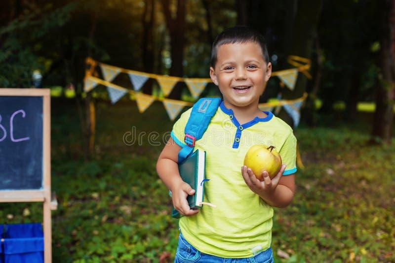 Liten lycklig pojke med ryggsäcken och notepaden tillbaka skola till Begreppet av utbildning, skola, barndom arkivfoto