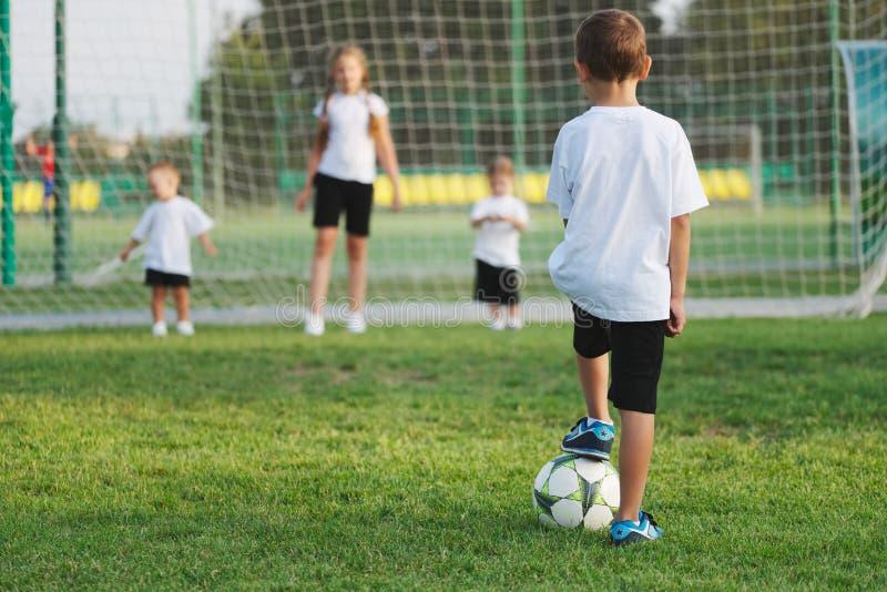 Liten lycklig pojke på fotbollfält arkivfoton