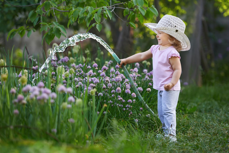 Liten lycklig trädgårdsmästare som bevattnar lökar royaltyfri bild
