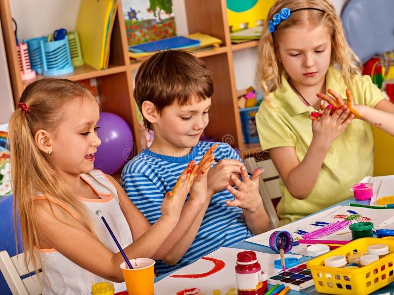 Liten målning för studentflickafinger i konstskolagrupp royaltyfria foton