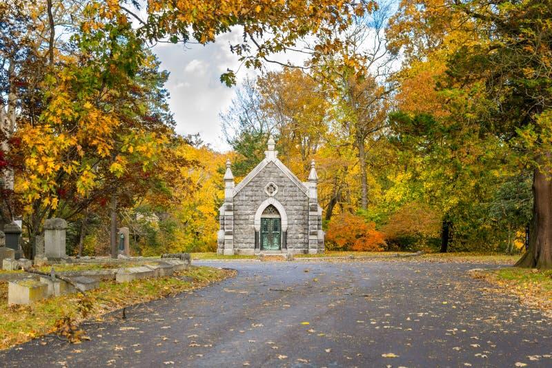 Liten mausoleum på Sleepy Hollowkyrkogården som omges av höstlig nedgånglövverk, Upstate New York, NY, USA royaltyfria foton