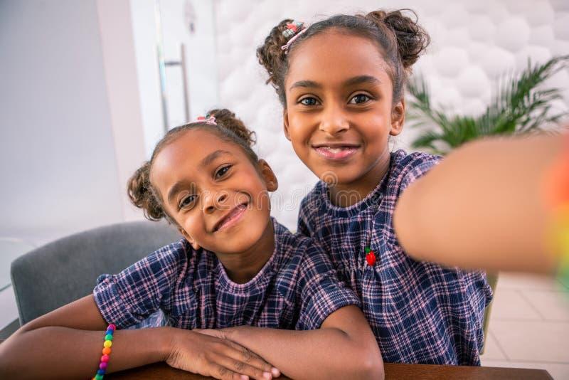 Liten mer ung sibling som bär det ljusa armbandet som poserar för foto med systern fotografering för bildbyråer