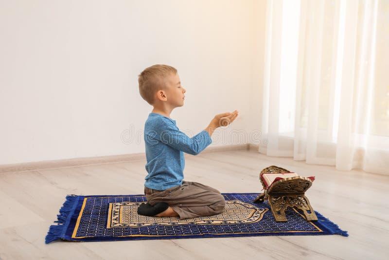 Liten muslimsk pojke med Koranen som ber på filten royaltyfri bild