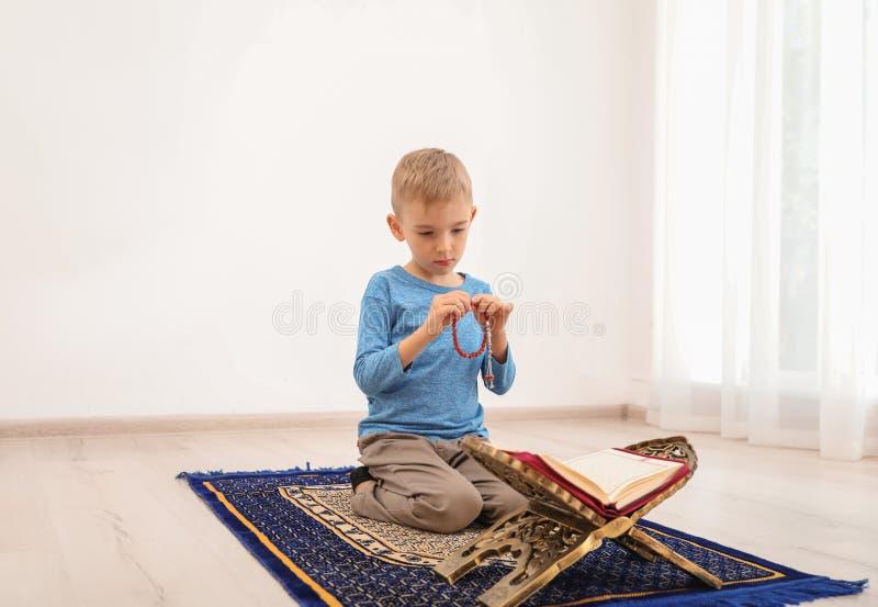 Liten muslimsk pojke med misbaha och att be för Koranen fotografering för bildbyråer