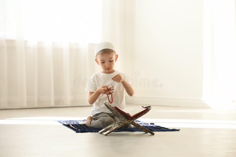 Liten muslimsk pojke med misbaha och Koranen som ber på filten arkivfoton